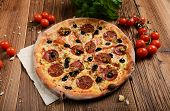stock photo of salami  - Tasty pizza with salami and olives on old wooden background - JPG
