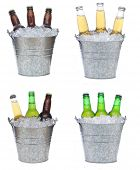 Four buckets holding three each of different beer bottles in ice. The bottles are covered with conde