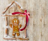 image of gingerbread house  - Gingerbread man in house on wooden table - JPG