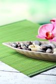 Spa stones and candle in decorative bowl, on wicker mat, on color wooden background