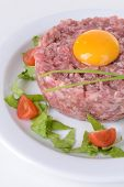 Delicious steak tartare with yolk on plate close-up
