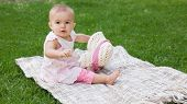 Full length of a cute baby sitting on blanket at the park