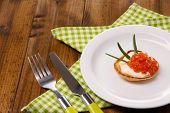 Pancake with red caviar and mayo, green onion, on plate, on color napkin, on wooden background