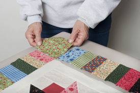 picture of cornerstone  - A quilter arranges a square of fabric for the cornerstone of a quilt top border - JPG