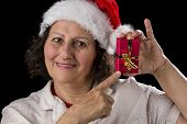 Smiling Aged Woman Holding And Pointing At Red Gift.