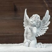 Little White Guardian Angel In Snow. Christmas Decoration