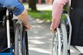 stock photo of hospice  - Couple of friends on a wheelchair horizontal - JPG