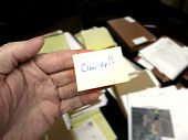 Messy office with hand holding note saying Clean Up