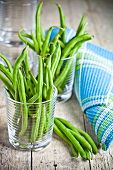 green string beans in glasses on rustic wooden background