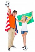 Excited football fan couple holding usa and brazils flag on white background
