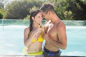 Smiling romantic young couple with champagne flutes by swimming pool