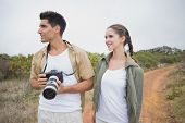 Portrait of hiking young couple holding camera on mountain terrain
