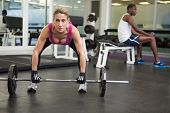 Portrait of a fit young woman lifting barbell in the gym