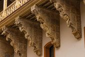 pic of corbel  - original corbel decoration in La Salina Palace courtyard with twisted carved bodies in Salamanca Spain
