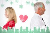 Couple not talking with broken heart between them against snowflakes and fir trees in green