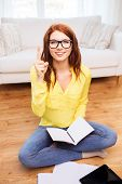 home, education, technology and idea concept - smiling teenage girl sitting on the floor with tablet