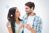 Happy young couple holding new house key against snow falling