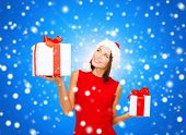 christmas, holidays, valentine's day, celebration and people concept - smiling woman in red dress with gift box over blue snowy background