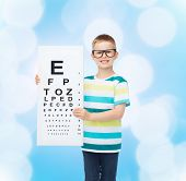 vision, health, childhood, ophthalmology and people concept - smiling little boy in eyeglasses with with eye chart over blue background