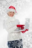 Festive woman using laptop smiling at camera against snowflakes on silver