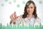 Portrait of businesswoman pointing her finger at camera against snowflakes and fir trees in green