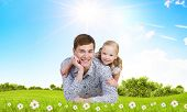 Happy family of father and daughter lying on green grass