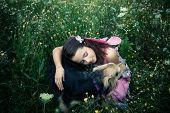 image of lost love  - girl like a fairy sitting in grass meadow  hugs lost dog  - JPG