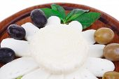 diet products : salted greek feta white cheese with olives and basil leaves sliced on wood isolated