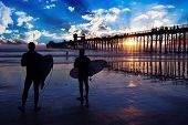 Surfers at sunset. Two surfers with boards silhouetted watch a colorful and reflective sunset near t