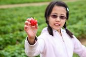 Girl Holding Up A Strawberry