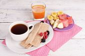 Slices of fruits with crispbreads and cup of tea on wooden table