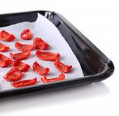 Sun dried tomatoes on drying tray, isolated on white