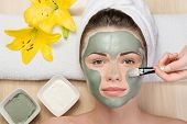 Beautiful girl with a towel on her head applying facial clay mask
