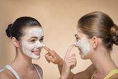 Two beautiful girls applying facial cream mask
