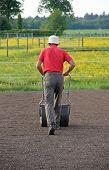 Man Flattening The Soil For Preparing Garden Lawn