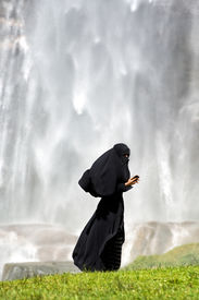 pic of burka  - Islamic woman dressed in a full burka standing on green grass using a smartphone side view with copyspace above