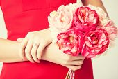 woman hands with bouquet of flowers and wedding ring.