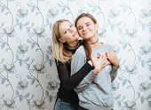 Lifestyle portrait of two young best friends hipster women hugging and posing against a wall indoors