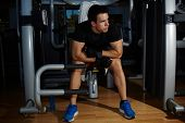 Full length portrait of young athlete seated on gym equipment and taking a break after workout