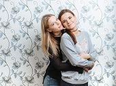 Lifestyle portrait of two young best friends hipster women hugging indoors
