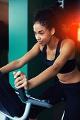 Half length portrait of cheerful happy woman with afro hair working out on spinning bike at gym