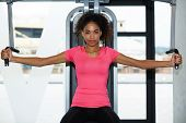 Attractive afro american woman working out on simulator weights machine at gym