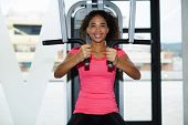 Pretty young woman exercising on simulator weights machine at fitness center