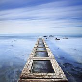 Wooden Pier Or Jetty On A Blue Ocean In The Morning.long Exposure