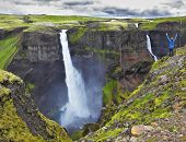 Spectacular waterfall Hayfoss in Iceland. Delighted woman - tourist in blue jacket standing on the edge of the cliff