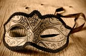 a carnival mask on a rustic wooden surface in sepia toning