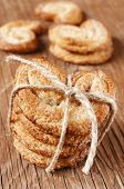 some palmeras, spanish palmier pastries, tied with a string on a rustic wooden table