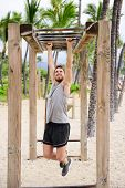 Fitness man on monkey bars fitness station gym. Strong male trainer training on brachiation ladder outdoors equipment as part of crossfit workout routine.