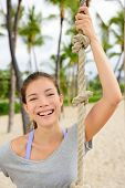 Fitness girl portrait - healthy fit woman smiling. Adorable mixed race asian chinese female athlete holding crossfit climbing rope on outdoor beach gym outside.