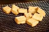 foto of stinky  - Stinky tofu on a metal oil screen - JPG
